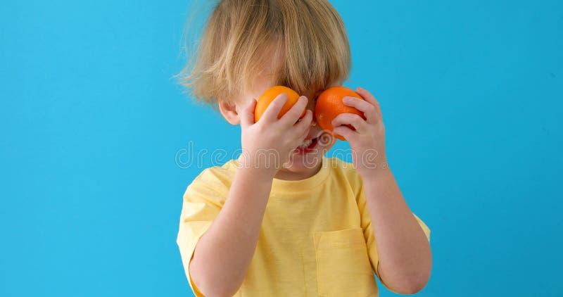 Ребенк с tangerines небольшой мальчик с мандаринами стоковые изображения