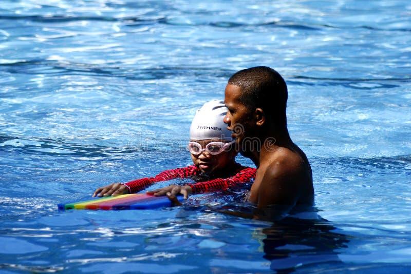 Ребенк учит как поплавать с помощью тренеру заплывания стоковое фото
