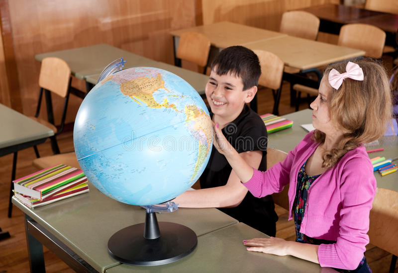 Ребенокы школьного возраста исследуя глобус в классе стоковое изображение
