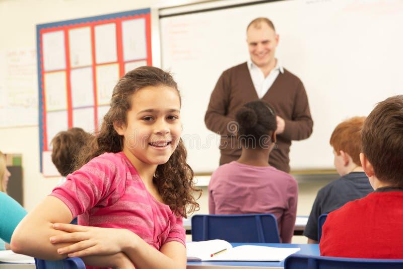 ребенокы школьного возраста класса изучая учителя стоковое изображение