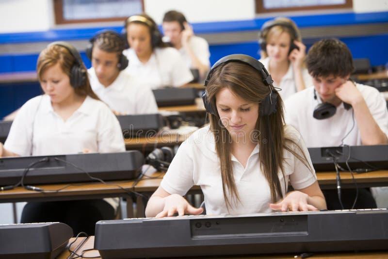 ребенокы школьного возраста нот клавиатуры типа практикуя стоковая фотография