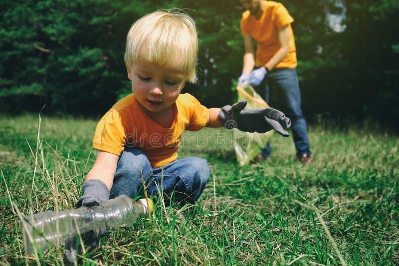 Ребенок активистов волонтеров и его отец в перчатках tidying вверх по хламу в концепции окружающей среды спасения парка или леса  стоковые изображения rf