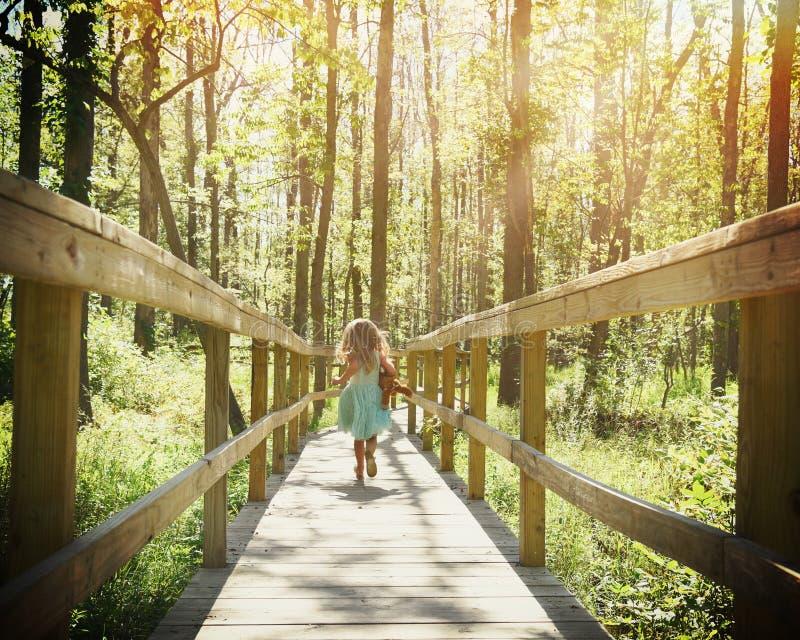 Ребенок бежать в древесинах с солнечным светом стоковые изображения rf