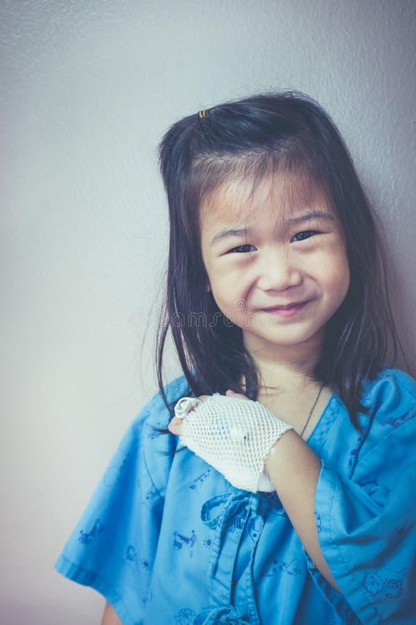 Ребенок болезни азиатский усмехаясь и показывая соляной потек iv на ее ha стоковые изображения