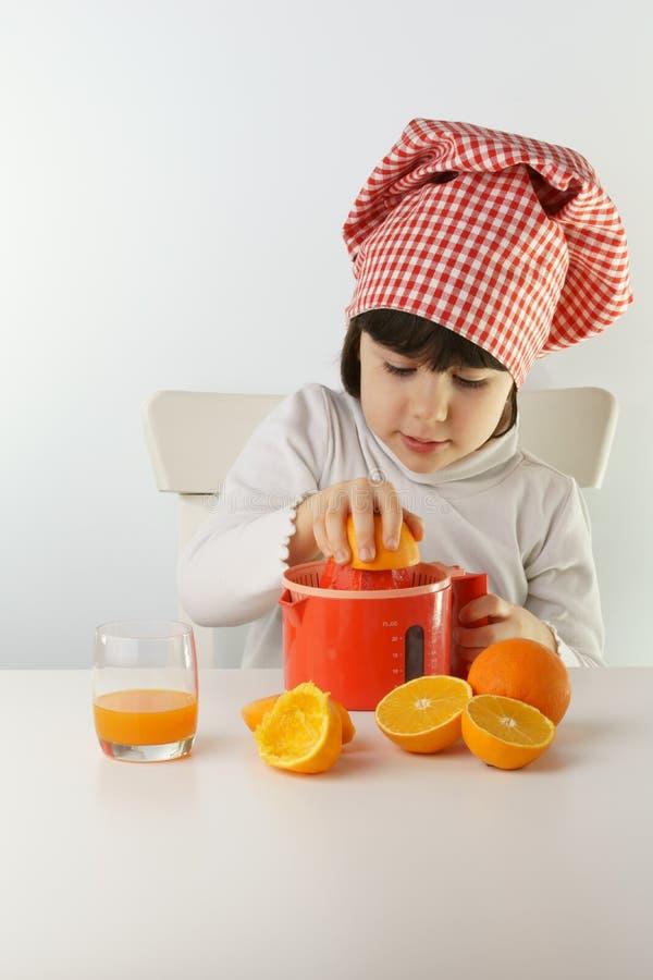 Ребенок варя с juicer стоковые фотографии rf