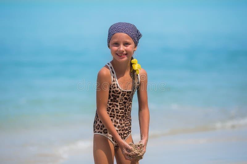 Ребенок, веселящийся на пляже, милая девушка играет в солнечный день, тропический пляж игра с песком и волнами стоковое изображение rf