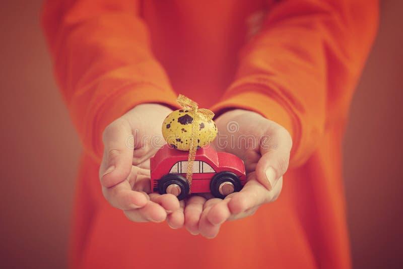 Ребенок вручает держать пасхальное яйцо на автомобиле на оранжевой предпосылке Принципиальная схема праздника стоковые изображения