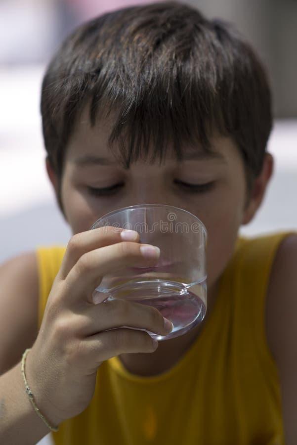 Ребенок выпивая стекло чисто воды стоковое изображение