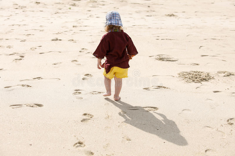 Ребенок выходя малые шаги в песок, играя barefoot стоковые изображения rf