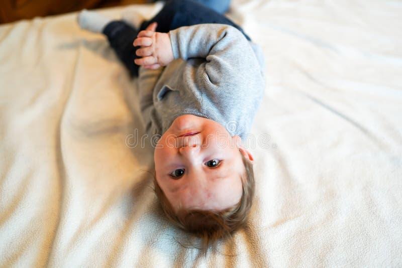 Ребенок в белой солнечной спальне Новорожденный ребенок ослабляя в кровати Питомник для маленьких ребят Утро семьи дома Ребенк но стоковая фотография rf