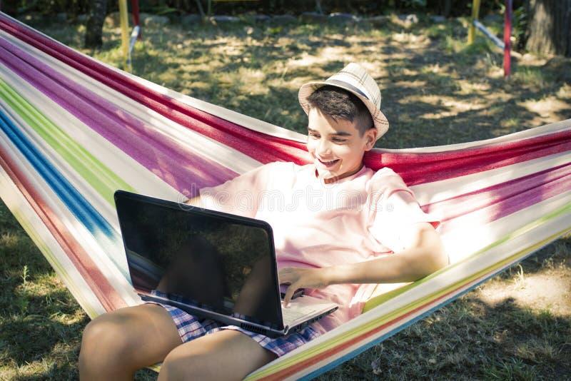 Ребенок в гамаке с компьютером стоковые фото