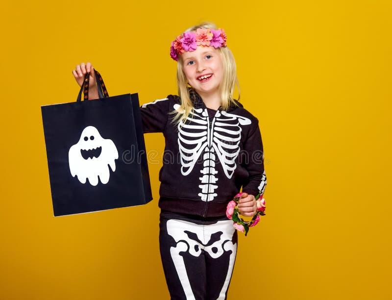 Ребенок в костюме хеллоуина изолированном на желтом цвете с хозяйственной сумкой стоковые изображения