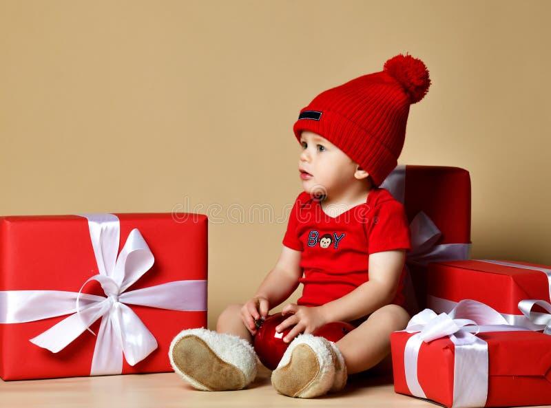Ребенок в красной шляпе со стогами присутствующих коробок вокруг сидеть на поле стоковые фото
