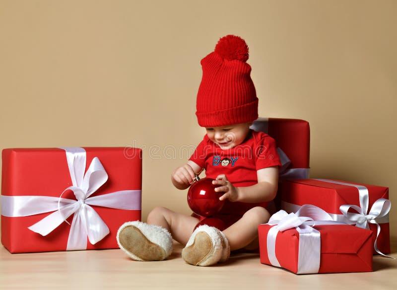 Ребенок в красной шляпе со стогами присутствующих коробок вокруг сидеть на поле стоковое изображение rf