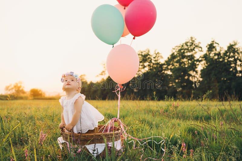 Ребенок в плетеной корзине с воздушными шарами на природе на лете стоковые изображения rf