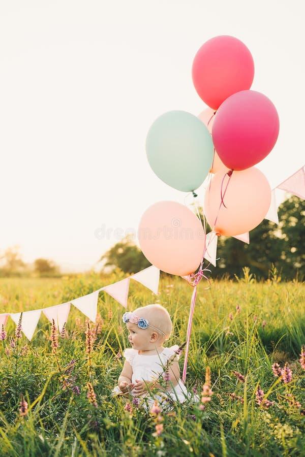 Ребенок в плетеной корзине с воздушными шарами на природе на лете стоковые изображения