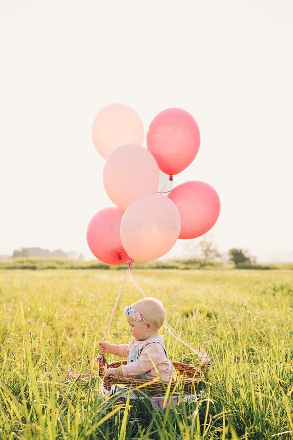Ребенок в плетеной корзине с воздушными шарами на природе на лете стоковое изображение rf