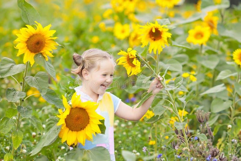 Ребенок в поле солнцецвета Дети с солнцецветами стоковое изображение rf
