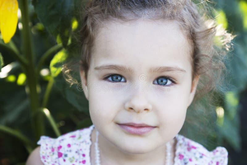 Ребенок в солнцецветах стоковое изображение rf