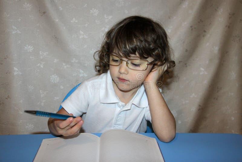 ребенок в стеклах с тетрадью и ручкой выполняет назначение домашней работы стоковое фото