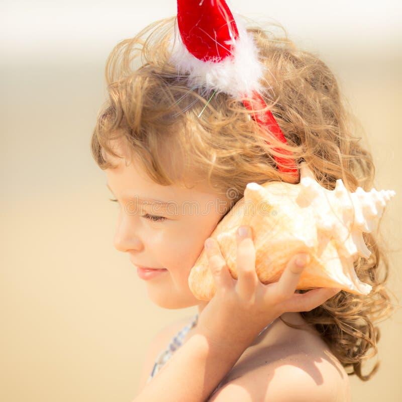 Ребенок в шляпе Санты на пляже стоковая фотография