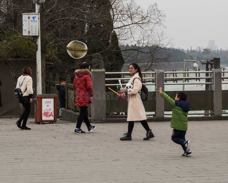 Ребенок гонит пузырь его мама дула стоковая фотография