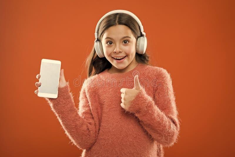 Ребенок девушки слушает наушники и смартфон музыки современные Получите подписку семьи музыки Доступ к миллионам песен стоковое фото rf