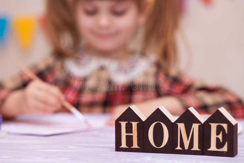 Ребенок делая домодельную поздравительную открытку Маленькая девочка красит сердце на домодельной поздравительной открытке как по стоковые изображения