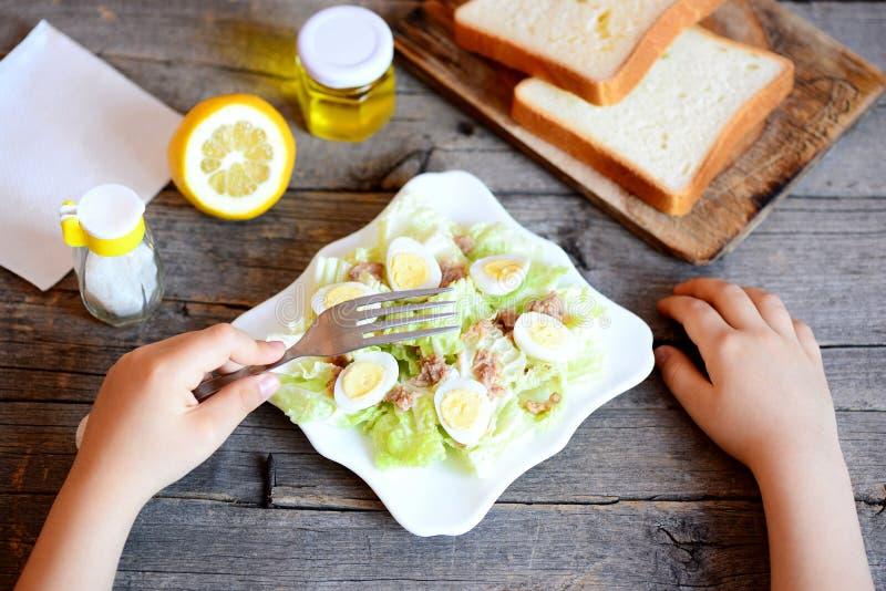 Ребенок держит вилку в его руке Малый ребенок ест салат с китайской капустой, законсервированным тунцом и яичками триперсток стоковое фото