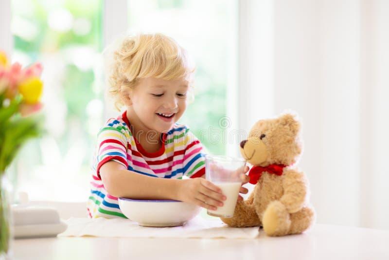 Ребенок есть ребенк завтрака с молоком и хлопьями стоковое изображение