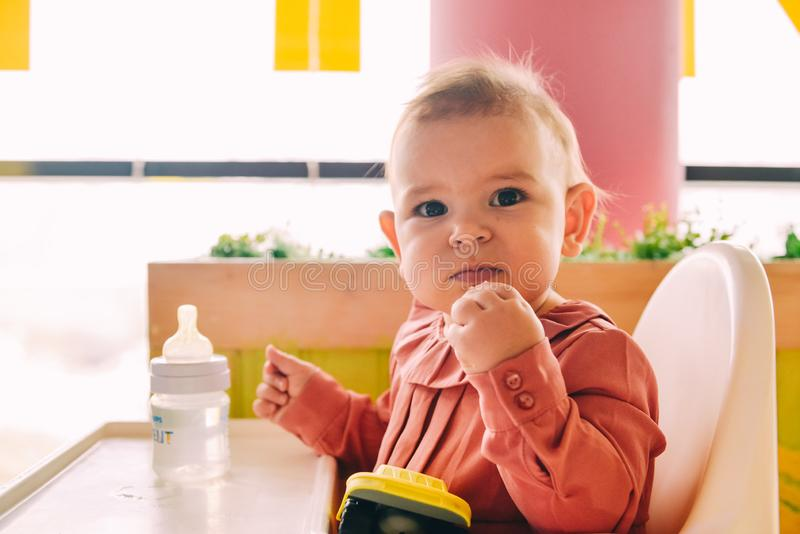 Ребенок есть сама на высоком стульчике стоковое фото rf