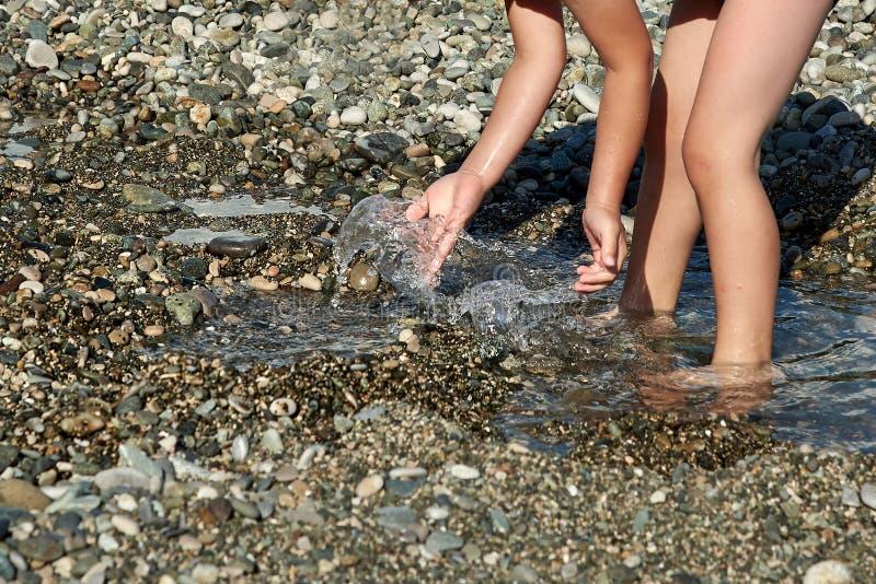 ребенок играя воду Лужица на каменном банке стоковая фотография