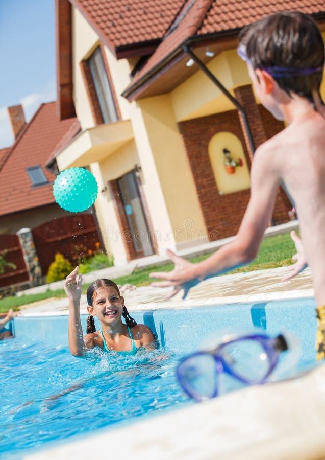 Ребенок играя в бассейне стоковая фотография