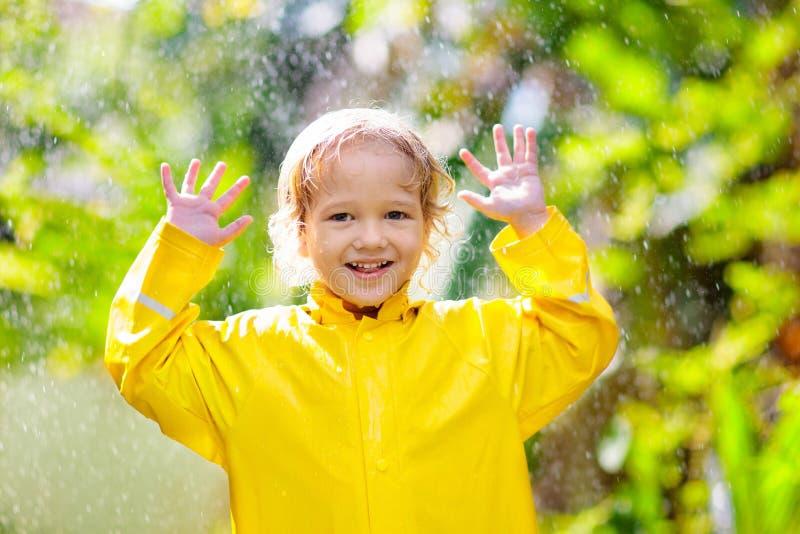 Ребенок играя в дожде Ребенк с зонтиком стоковые фото