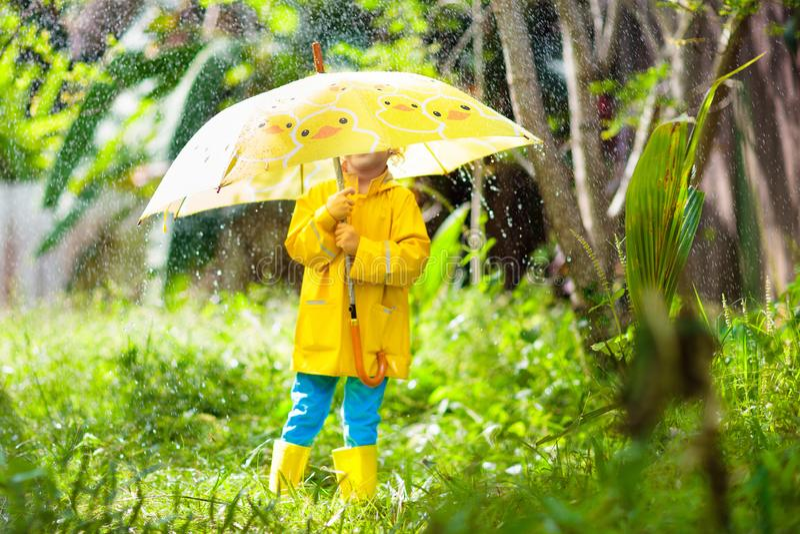 Ребенок играя в дожде Ребенк с зонтиком стоковое фото