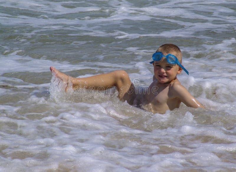 Ребенок играя в океане стоковая фотография rf