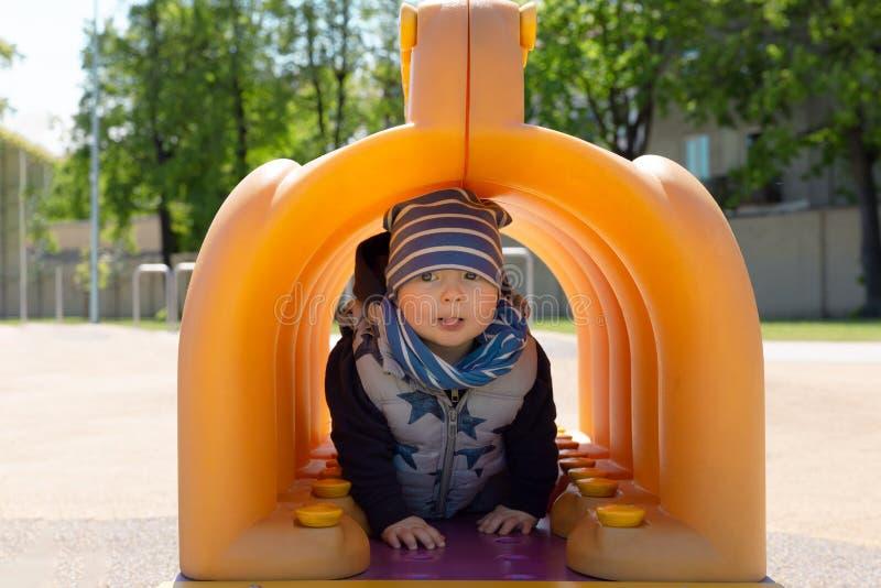 Ребенок играя в спортивной площадке, идя тоннеле ринва стоковая фотография rf
