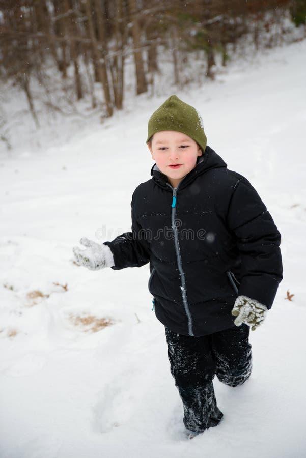 Ребенок играя в ходе снега стоковая фотография