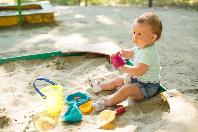 Ребенок играя в ящике с песком на на открытом воздухе спортивной площадке Ребенок с красочными игрушками песка Здоровый активный  стоковое изображение rf