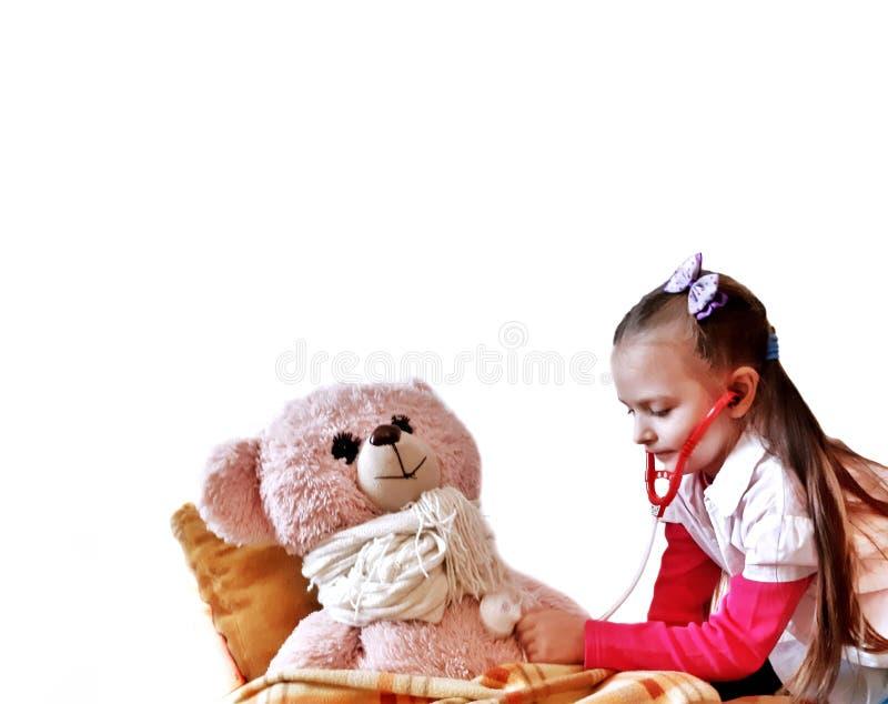 Ребенок играя доктора с плюшевым мишкой на белой предпосылке стоковые фотографии rf