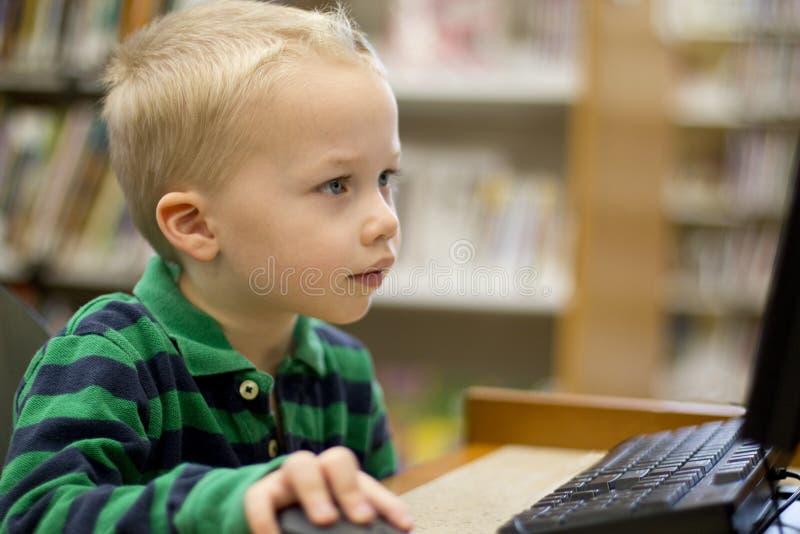 Ребенок играя на компьютере стоковые фотографии rf