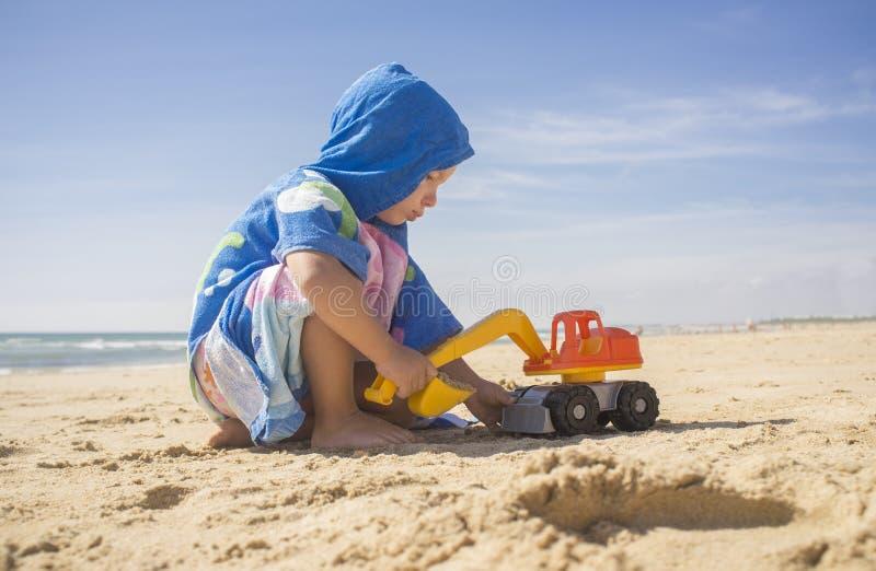 Ребенок играя на песке на пляже с игрушкой экскаватора стоковое фото rf