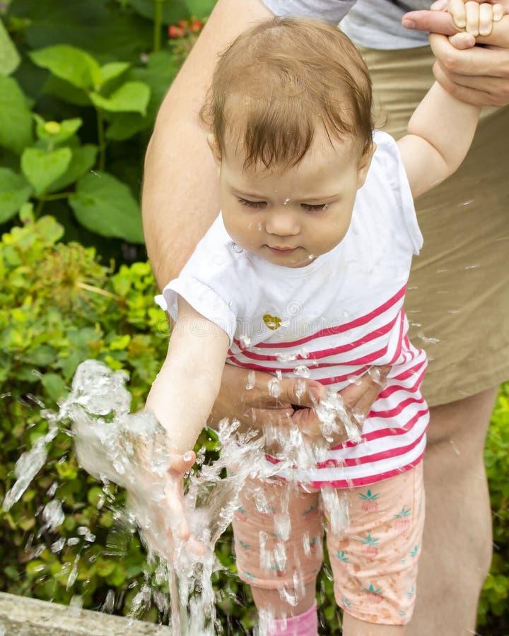 Ребенок играя с двигателями воды в фонтане Ребенок на прогулке в играх парка с водой, младенец взбирается в стоковая фотография rf