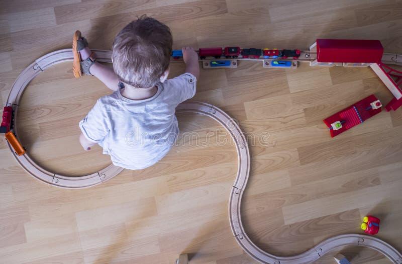 Ребенок играя с деревянным поездом игрушки стоковые фотографии rf