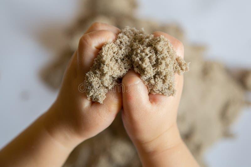 Ребенок играя с кинетическим песком Чувственные опыты младенца стоковые изображения