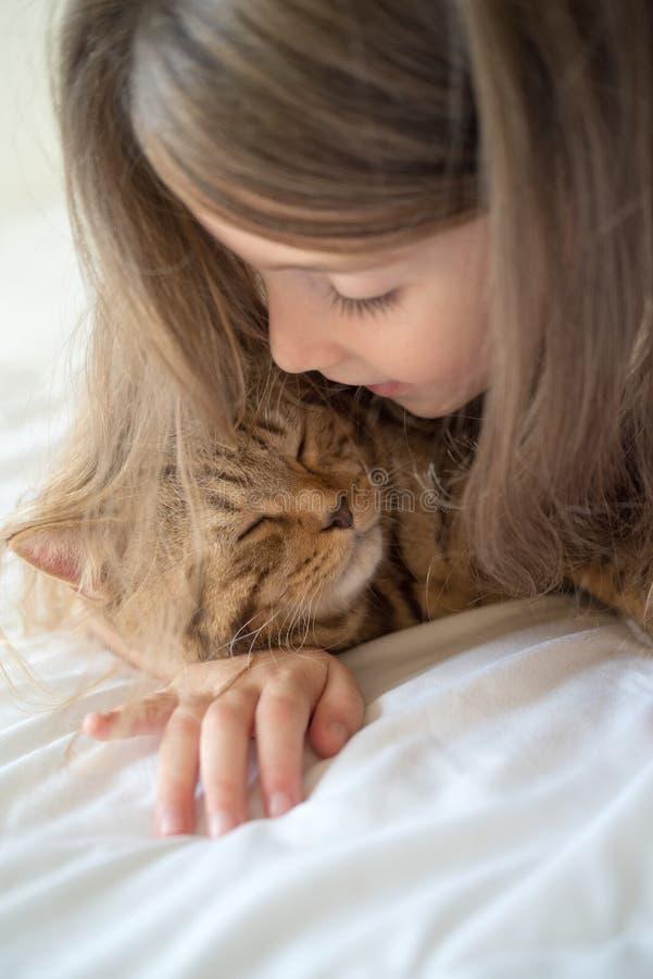 Ребенок играя с котом на кровати стоковые изображения rf