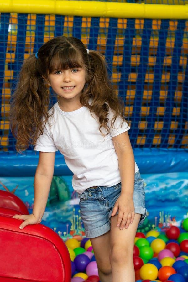 Ребенок играя с красочными шариками в бассейне шарика спортивной площадки Игрушки деятельности для маленького ребенка Эмоция счас стоковые фотографии rf