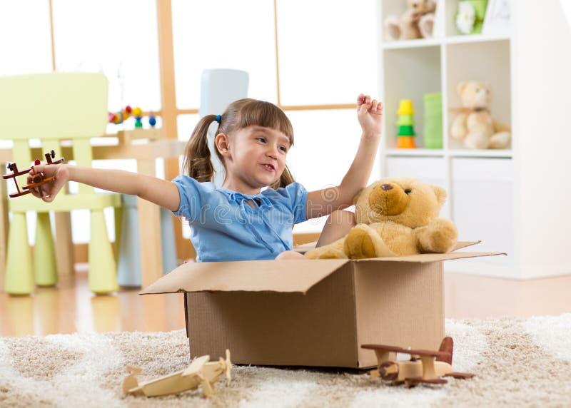 Ребенок играя с плоской игрушкой дома Концепция перемещения, свободы и воображения стоковое фото