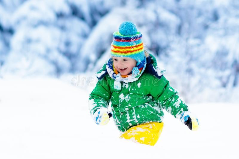 Ребенок играя с снегом в зиме малыши outdoors стоковые фотографии rf