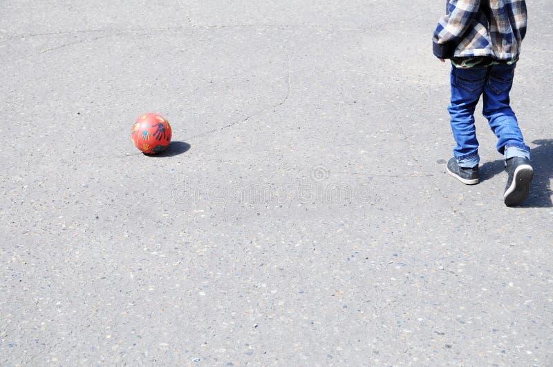 Ребенок играя футбол на асфальте, игроке футбольной команды, тренируя внешний, активный образ жизни стоковые изображения rf